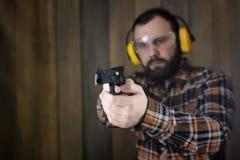 Mężczyzna z stawiającymi dalej ochronnymi gogle i uszaty szkolenie w pistoletowy sh Zdjęcie Stock