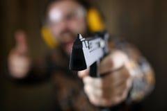 Mężczyzna z stawiającymi dalej ochronnymi gogle i uszaty szkolenie w pistoletowy sh Zdjęcia Stock