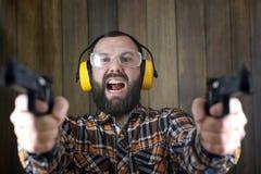 Mężczyzna z stawiającymi dalej ochronnymi gogle i uszaty szkolenie w pistoletowy sh Obrazy Stock