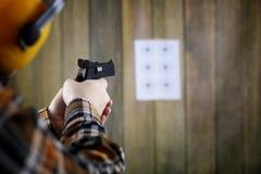 Mężczyzna z stawiającymi dalej ochronnymi gogle i uszaty szkolenie w pistoletowy sh Obrazy Royalty Free