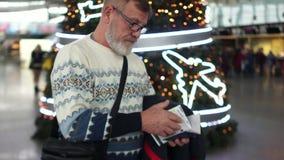 Mężczyzna z szarą brodą czekać na jego lot przyjeżdżać przy lotniskiem międzynarodowym podczas bożych narodzeń i nowego roku zdjęcie wideo