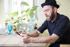 Mężczyzna z szczęśliwym patrzeje telefonem i mydlanymi bąblami kapeluszu i brody ja Zdjęcia Stock