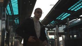 Mężczyzna z szkłami i torbami przy stacją kolejową sprawdza jego taborowego bilet i paszport zbiory