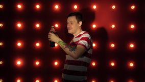 Mężczyzna z tatuażem pije odświeżającego napój Młoda caucasian samiec pije napój od butelki zbiory wideo
