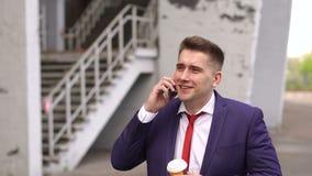 Mężczyzna z telefonem i filiżanką kawy na ulicie zbiory