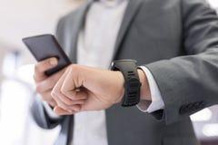 Mężczyzna z telefonem komórkowym łączył mądrze zegarek zdjęcie royalty free