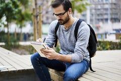 Mężczyzna z telefonem komórkowym dla prezentaci pracy projekta narządzania kursowej pracy domowej przed lekcjami zaczyna Zdjęcia Royalty Free