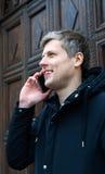 Mężczyzna z telefonem komórkowym i ono uśmiecha się Zdjęcie Royalty Free