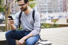 Mężczyzna z telefonem komórkowym i tematami dla artykułu tworzenia podczas gdy mieć pracy przerwę w uniwersytecie Obrazy Royalty Free