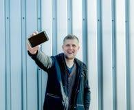 Mężczyzna z telefonem komórkowym na miastowym tle Obrazy Royalty Free