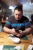 Mężczyzna z telefonem w pubie Obrazy Stock