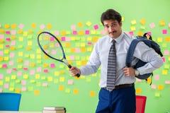 Mężczyzna z tenisowym kantem w biurze z wiele sprzeczny przeor zdjęcie stock