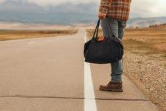 Mężczyzna z torbą w ręki odprowadzenia puszku halna droga Obraz Stock