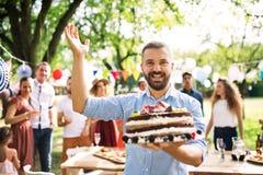 Mężczyzna z tortem na rodzinnym świętowaniu outside lub ogrodowym przyjęciu zdjęcie stock
