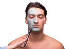 Mężczyzna z twarzy maską stosuje na bielu Fotografia Royalty Free