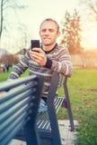 Mężczyzna z urządzeniem przenośnym w jesień parku Obraz Stock