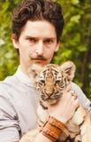 Mężczyzna z wąsy spojrzeniami w twarz tygrysi lisiątko Obraz Royalty Free