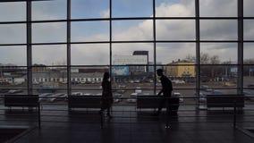 Mężczyzna z walizką przy lotniskiem, spotyka kobiety, kłębią i całują zbiory wideo