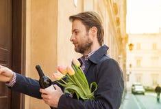Mężczyzna z wina i kwiatu bukieta dzwonienia doorbell Zdjęcia Stock