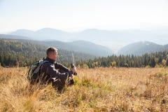Mężczyzna z wyposażeniem w poszukiwaniu trasy w górach obraz stock