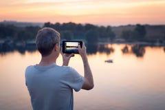 Mężczyzna z zakładką robi fotografii zmierzch obrazy stock