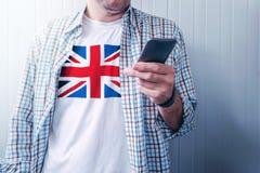 Mężczyzna z Zjednoczone Królestwo flaga na koszulowym używa telefonie komórkowym obrazy stock