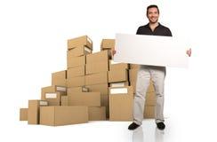 Mężczyzna z znakiem i stosy pudełka Zdjęcia Royalty Free