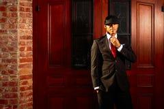 Mężczyzna załatwia krawat w kostium pozyci przed drewnianymi drzwiami Fotografia Royalty Free