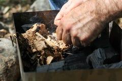 Mężczyzna zaświeca ogienia z krzemieniem Zdjęcie Stock