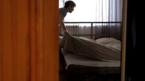 Mężczyzna za brąz zasłonami robi dwoistemu łóżku przeciw okno zbiory wideo