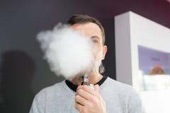 Mężczyzna zaciemniający za obłocznym odparowalnika dymem obraz royalty free