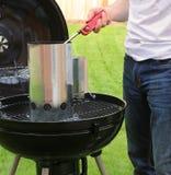 Mężczyzna zaczyna BBQ ogienia z zapalniczką Zdjęcie Stock