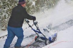Mężczyzna zaczyna snowblower na podjeździe obrazy stock