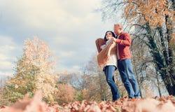 Mężczyzna zakrywa jego żon ramiona z ciepłą chustą w jesień parku zdjęcie royalty free