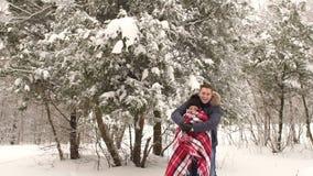 Mężczyzna zakrywa jego dziewczyny z koc w śnieżnym parku zdjęcie wideo