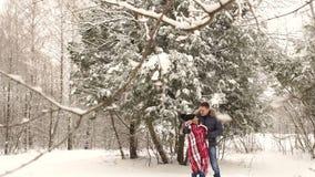 Mężczyzna zakrywa jego dziewczyny z koc w śnieżnym parku zbiory wideo
