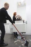 Mężczyzna Zamiata Podczas gdy fryzjer Daje ostrzyżeniu Starsza kobieta zdjęcie stock