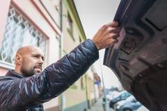 Mężczyzna zamyka frontowego kapiszon samochód obraz stock