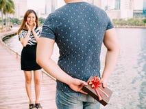 Mężczyzna zaskakuje jego dziewczyny dawać out prezentowi - miłości i związku pojęcie Zdjęcie Stock