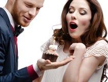 Mężczyzna zastanawia się jego dziewczyny z urodzinowym kulebiakiem Zdjęcie Royalty Free