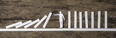 Mężczyzna zatrzymuje domino skutek Zdjęcie Stock