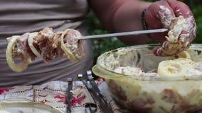 Mężczyzna zawiązuje mięso na skewer Wyśmienicie apetyczni kawałki świeży mięso zawiązywali na skewers przygotowywających dla gril zbiory