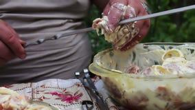 Mężczyzna zawiązuje mięso na skewer Wyśmienicie apetyczni kawałki świeży mięso zawiązywali na skewers przygotowywających dla gril zbiory wideo