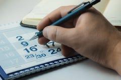 Mężczyzna zaznacza znacząco dzień w kalendarzu obraz stock