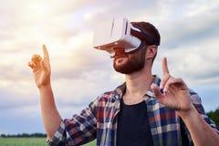 Mężczyzna zbliża przedmiot w VR szkłach podczas gdy stojący w zieleni polu Obraz Royalty Free
