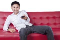 Mężczyzna zmiany kanał telewizyjny z telefonem komórkowym Zdjęcia Stock