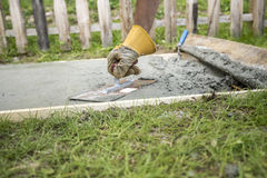 Mężczyzna zrównuje powierzchnię beton p z ochronnymi rękawiczkami Obraz Royalty Free