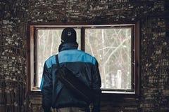 Mężczyzny adventureron wyprawy rekonesansowa stara chałupa w lasowym mężczyźnie w niebieskiej marynarki pozycji w drzwi i patrzeć obrazy royalty free