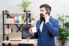 Mężczyzny biznesmena chwyta brodata filiżanka i smartphone Kawa jest przyrzeczeniem pomyślne negocjacje Kofeina uzale?niaj?ca si? obrazy royalty free