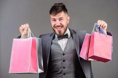 Mężczyzny brodaty elegancki biznesmen niesie torby na zakupy na popielatym tle Cieszy się robiący zakupy zyskowne transakcje czar zdjęcia royalty free